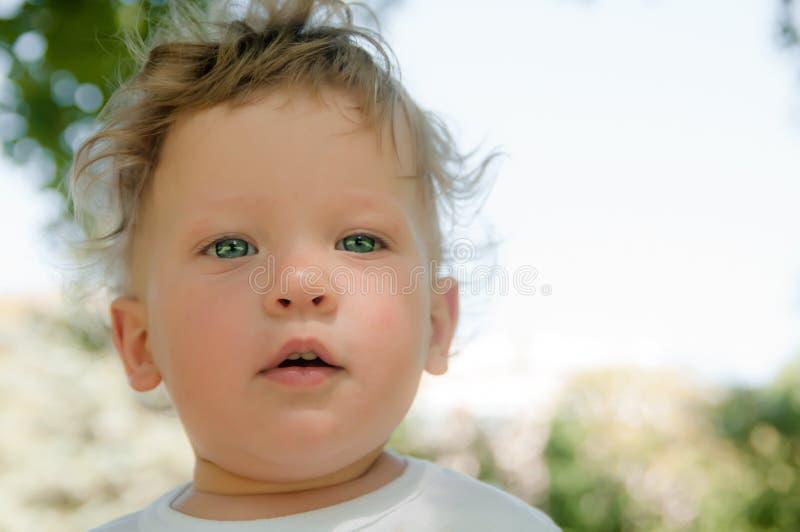 De een weinig krullende jongen in een witte T-shirt bekijkt direct me stock foto