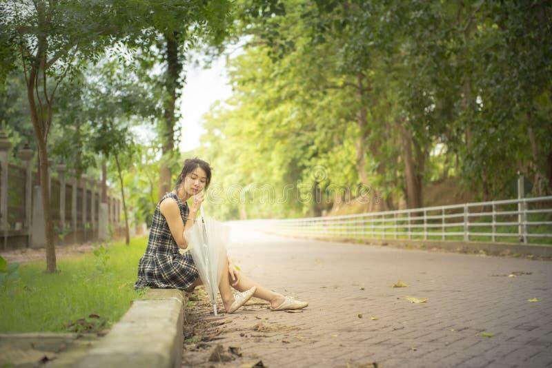 De eenzame Aziatische vrouw tiener in toevallige kleding zit door gang met grote de greepparaplu van de glimlachhand in openbare  stock afbeeldingen