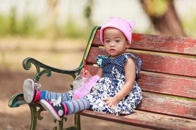 De eenzame Aziatische zitting van het babymeisje met drank stock afbeeldingen