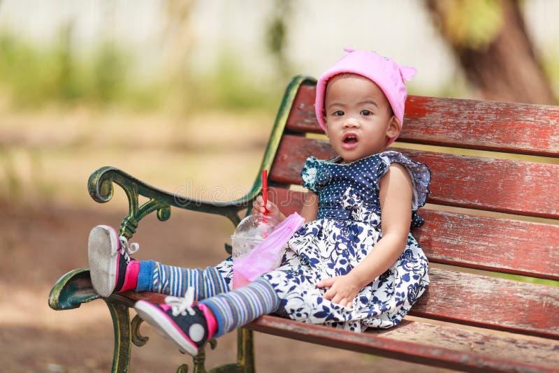 De eenzame Aziatische zitting van het babymeisje met drank royalty-vrije stock afbeeldingen