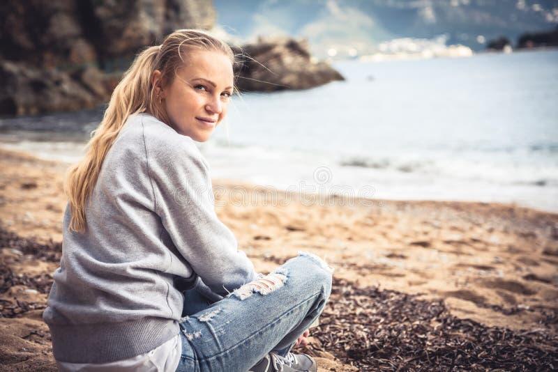 De eenzame het glimlachen zitting van de vrouwentoerist op strand in donkere dag en het bekijken camera stock afbeeldingen
