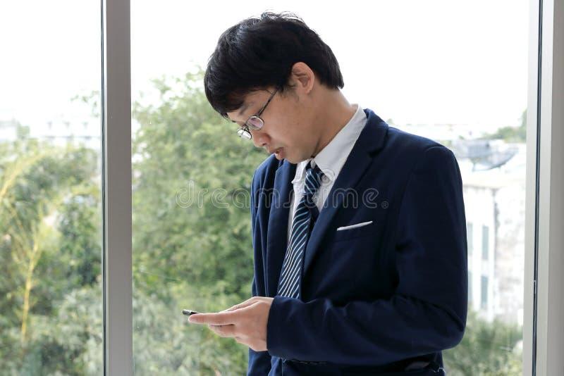 De eenzame jonge Aziatische mens die in kostuum mobiele smartphone dient binnen bureau in kijken stock afbeelding