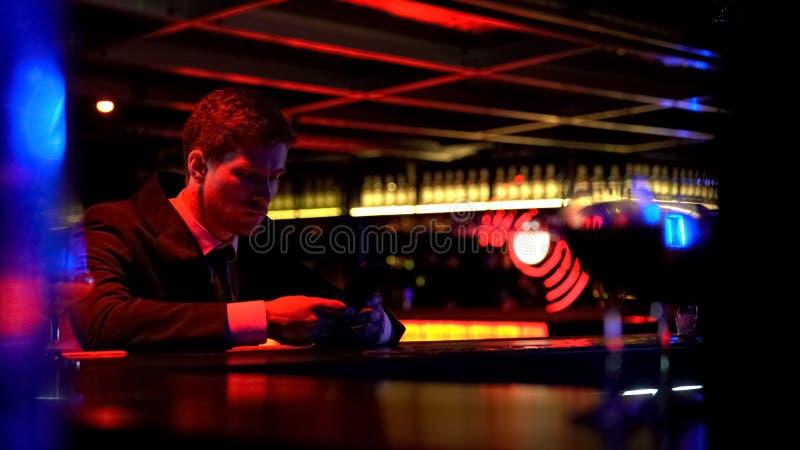 De eenzame mens bored bij barteller, het doorbladeren sociale media, gebrek aan mededeling stock afbeeldingen