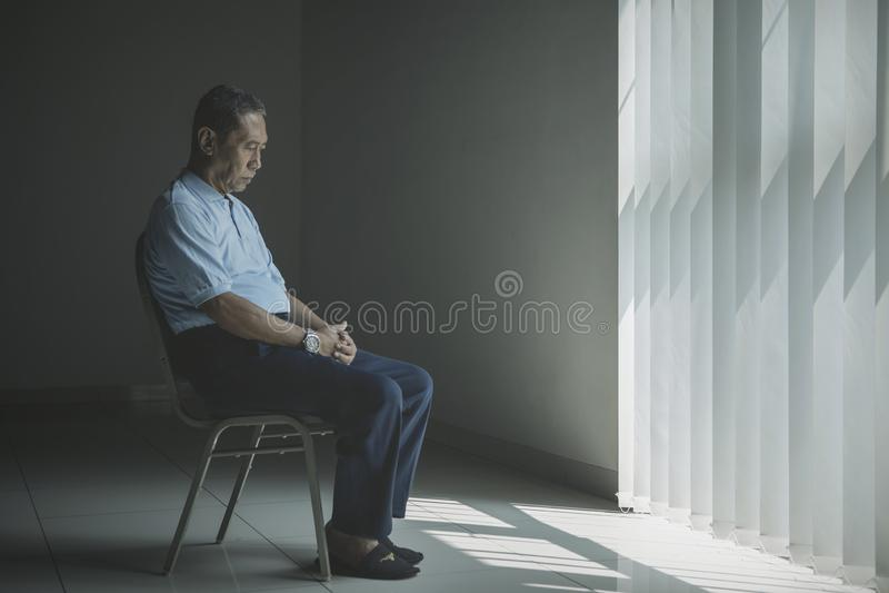 De eenzame oude mens kijkt droevig dichtbij het venster stock foto's