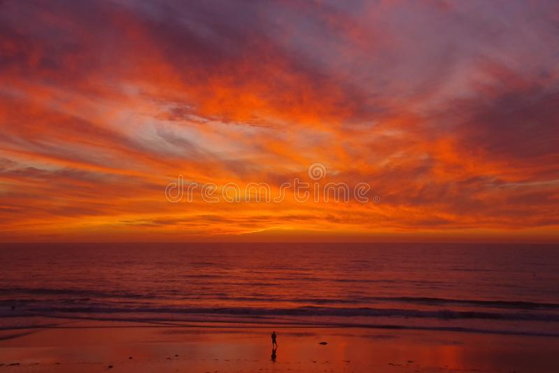 De eenzame persoon op strand ziet een glorierijke zonsondergang onder ogen stock afbeelding