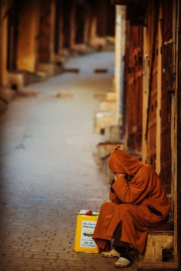 De eenzame slechte mens in stille ochtend en de lege straat in oude markt van Fes Medina met traditionele mousseline kleden zich, royalty-vrije stock foto's