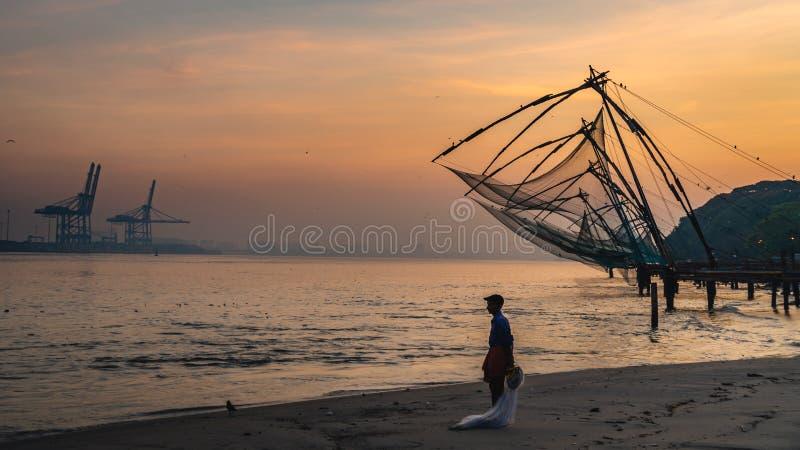 De eenzame visnetten van Chinese van de mensenvisser tijdens de Gouden Uren bij Fort Kochi, Kerala, India stock fotografie