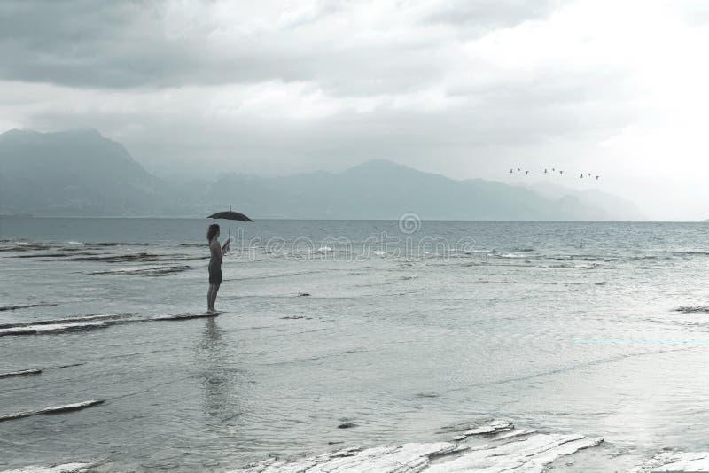 De eenzame vrouw bekijkt oneindigheid en niet besmette aard op een stormachtige dag stock fotografie