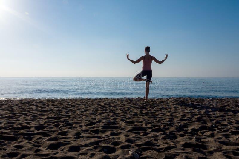De eenzame yoga van de persoonspraktijk op het strand door overzeese kust op een zonnige dag royalty-vrije stock fotografie