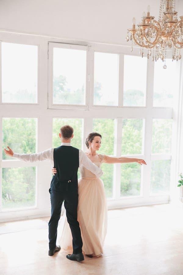 De eerste Dans van het Huwelijk de dansen van het huwelijkspaar op de studio De dag van het huwelijk Gelukkige jonge bruid en bru royalty-vrije stock foto's