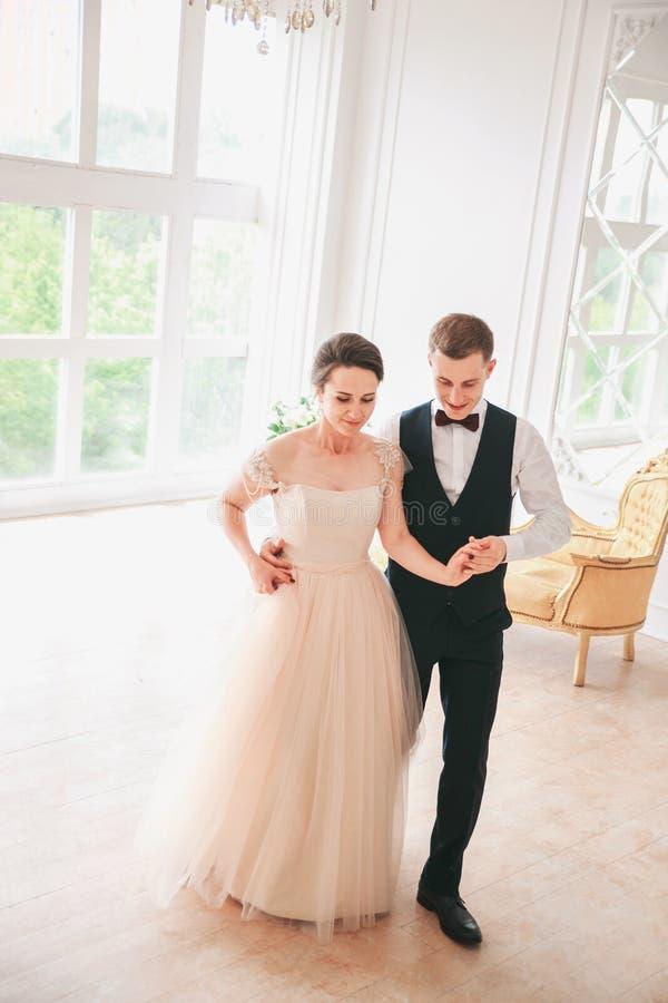 De eerste Dans van het Huwelijk de dansen van het huwelijkspaar op de studio De dag van het huwelijk Gelukkige jonge bruid en bru stock afbeelding