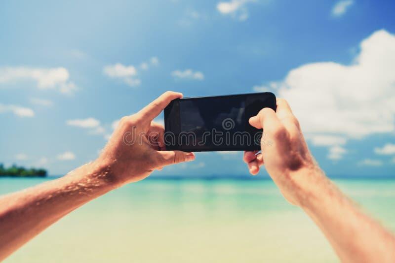 De eerste mensen die van de oogmening slimme telefoon, cellphone op het strand op mooie aard als achtergrond, overzees en blauwe  stock foto