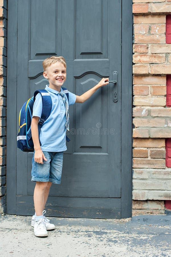 De eerste-nivelleermachine met een rugzak is bij de deur van de school De eerste vraag eind van het schooljaar honger voor kennis royalty-vrije stock fotografie