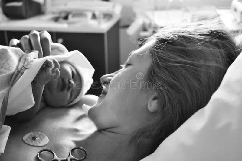 De eerste ogenblikken van moeder en pasgeboren na bevalling stock afbeeldingen