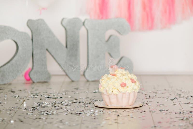 De eerste verjaardags roze cake met bloemen voor weinig babymeisje en de decoratie voor cake breken Grote zilveren brieven ÉÉN en stock foto's