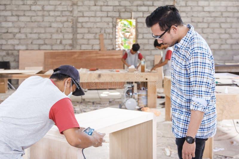 De eigenaar die van de meubilairfabriek zijn arbeider controleren bij het werkruimte stock afbeelding