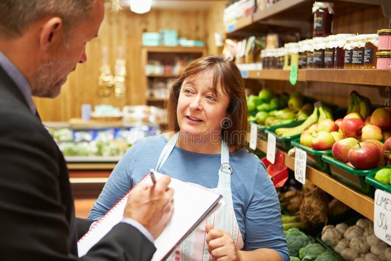 De Eigenaar van Bankdirecteurmeeting with female van Landbouwbedrijfwinkel stock foto