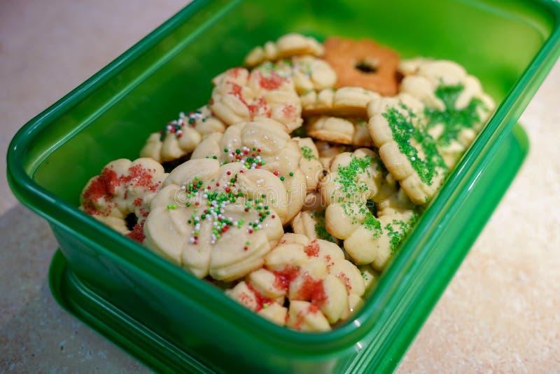 De eigengemaakte boterdiekoekjes van spritzkerstmis in een groene plastic container voor gemakkelijk vervoer aan een partij worde royalty-vrije stock afbeelding