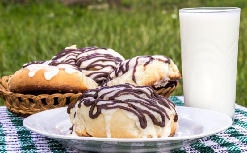 De eigengemaakte broodjes van de cinnabonkaneel met roomkaas verglazen en chocoladesuikerglazuur en glas melk stock fotografie