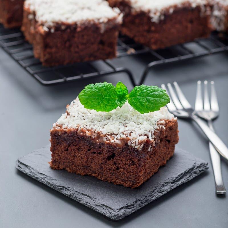 De eigengemaakte brownie met kokosnoot schilfert, Zweeds dessert Karleksmums, besnoeiing in vierkante porties, op een steenplaat  stock foto's