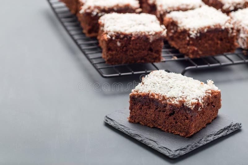 De eigengemaakte brownie met kokosnoot schilfert, Zweeds dessert Karleksmums, besnoeiing in vierkante porties, op steenplaat en k royalty-vrije stock fotografie