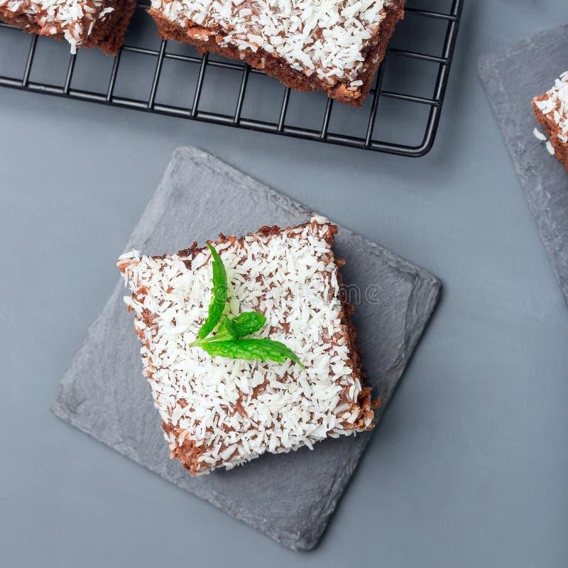 De eigengemaakte brownie met kokosnoot schilfert, Zweeds dessert Karleksmums, besnoeiing in vierkante porties, op steenplaat en k stock fotografie