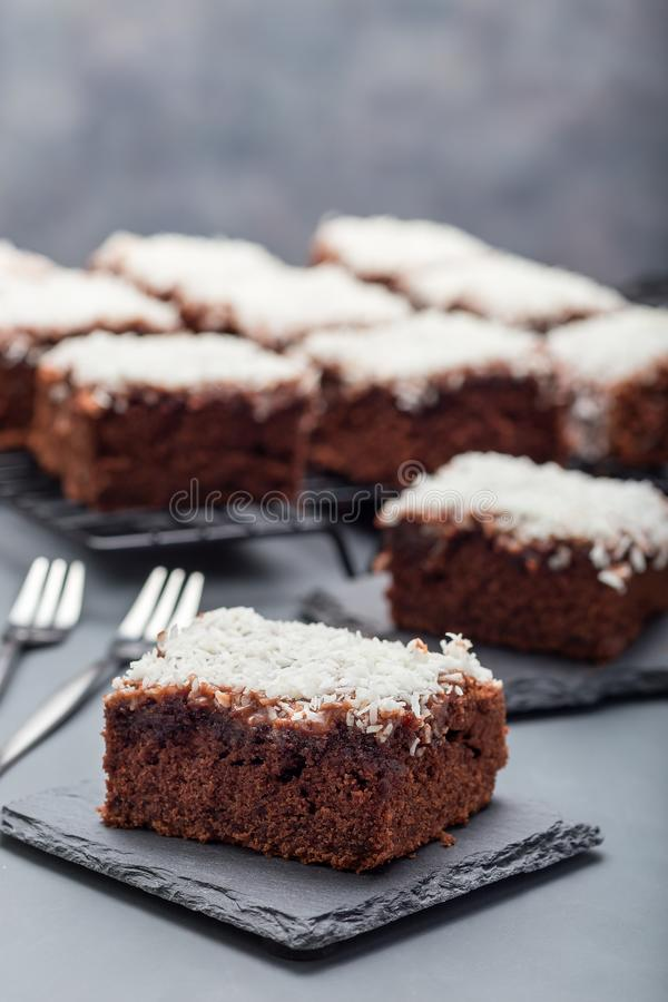 De eigengemaakte brownie met kokosnoot schilfert, Zweeds dessert Karleksmums, besnoeiing in vierkante porties, op verticale steen royalty-vrije stock fotografie