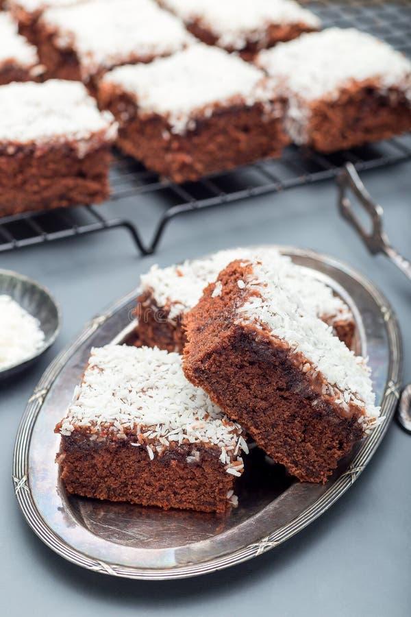 De eigengemaakte brownie met kokosnoot schilfert, Zweeds dessert Karleksmums, besnoeiing in vierkante verticale porties af, royalty-vrije stock fotografie