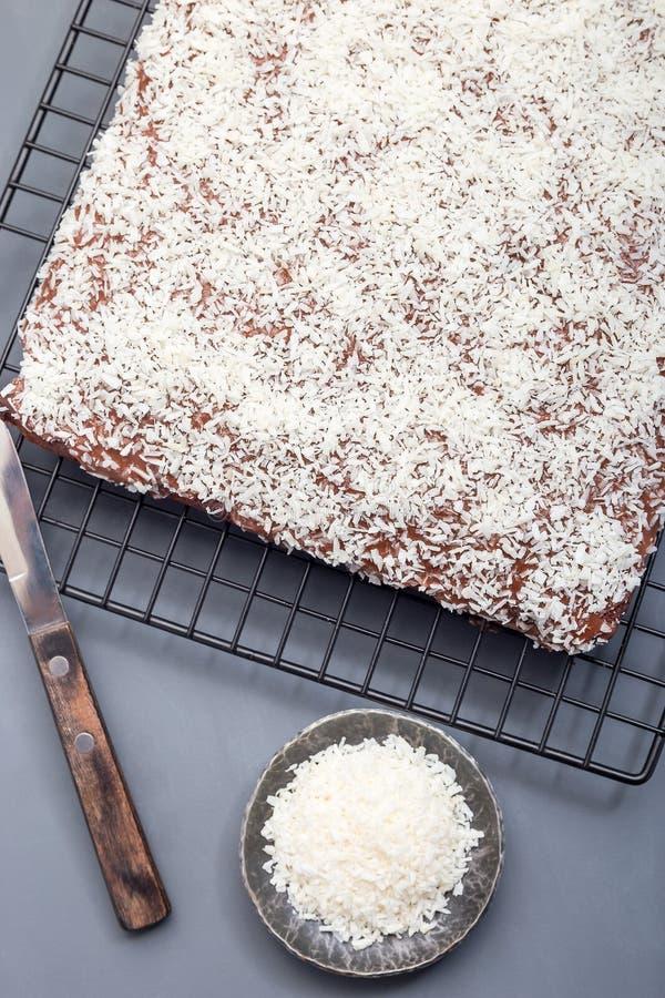 De eigengemaakte brownie met kokosnoot schilfert, Zweedse dessertkarleksmums, op een koelrek, verticaal, hoogste mening af stock foto's