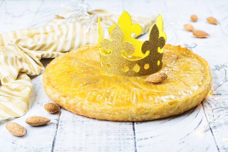 De eigengemaakte cake van Galette des Rois met met de hand gemaakte koningenkroon Traditionele Franse Epiphany-cake met grondaman stock afbeelding