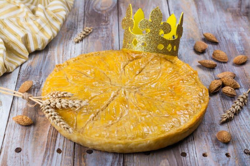 De eigengemaakte cake van Galette des Rois met met de hand gemaakte koningenkroon Traditionele Franse Epiphany-cake met grondaman stock foto