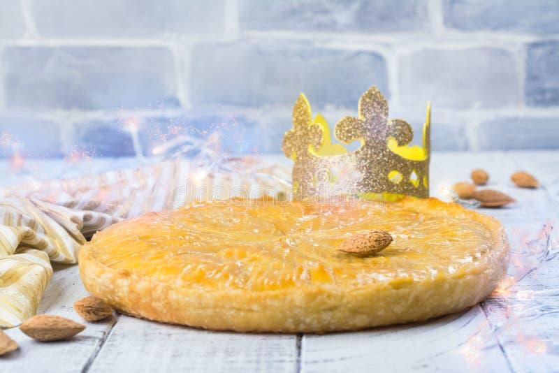 De eigengemaakte cake van Galette des Rois met met de hand gemaakte koningenkroon Traditionele Franse Epiphany-cake met grondaman stock foto's