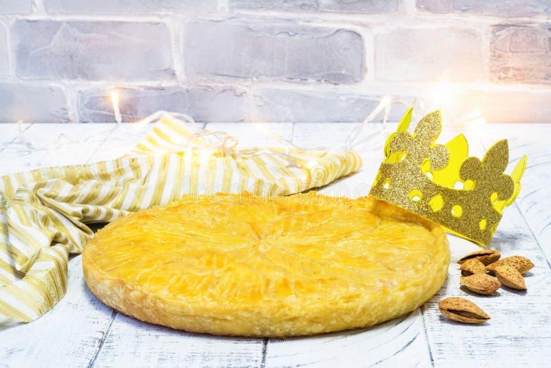 De eigengemaakte cake van Galette des Rois met met de hand gemaakte koningenkroon Traditionele Franse Epiphany-cake met grondaman stock fotografie