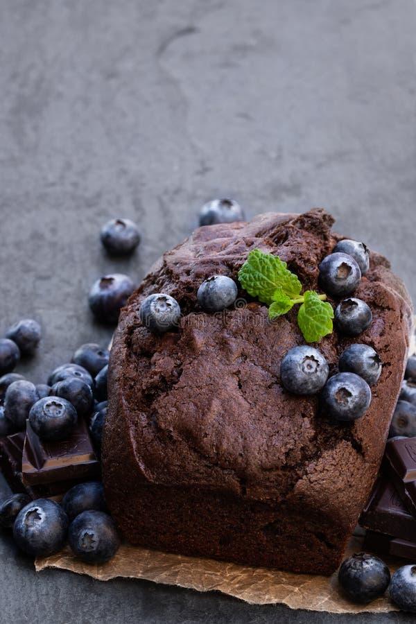 De eigengemaakte cake van het chocoladebrood met bosbes op zwarte steenachtergrond stock foto's
