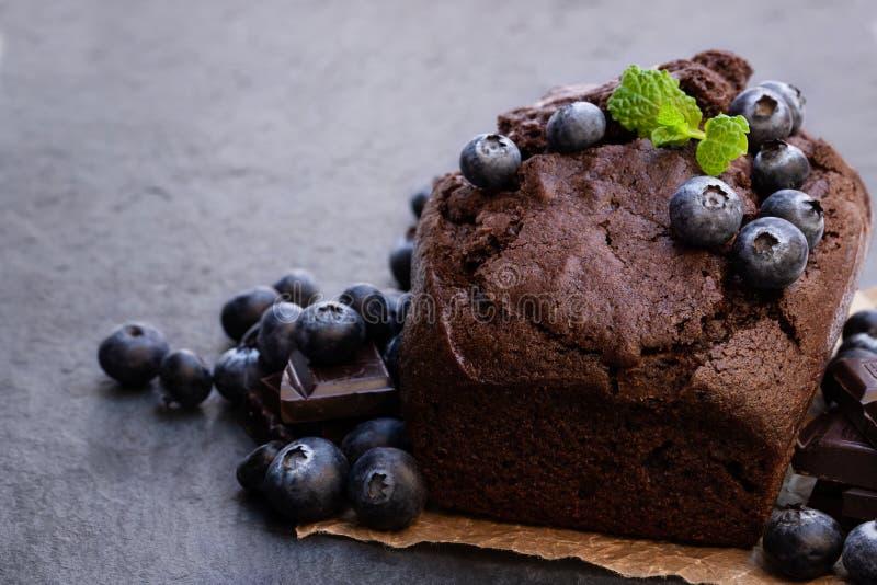 De eigengemaakte cake van het chocoladebrood met bosbes op zwarte steenachtergrond stock afbeelding