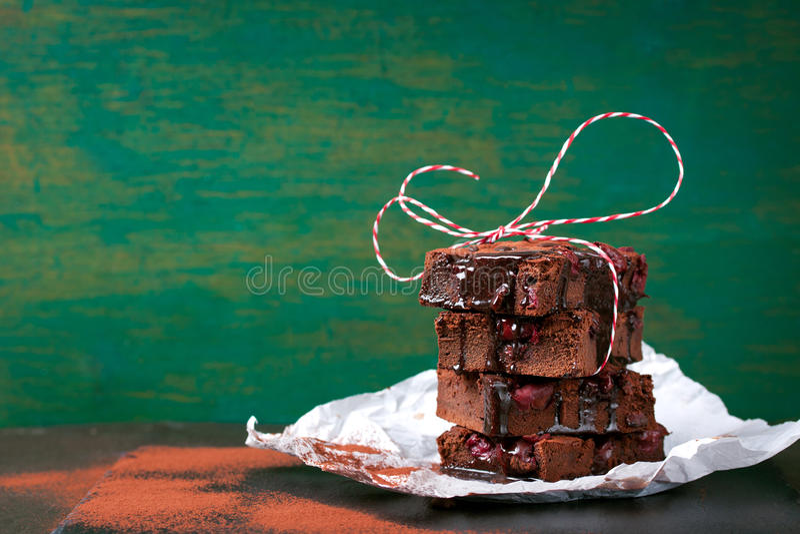 De eigengemaakte cakes van chocolade zoete brownies met kers en chocoladesaus of stroop op een donkere horizontale achtergrond, royalty-vrije stock foto's