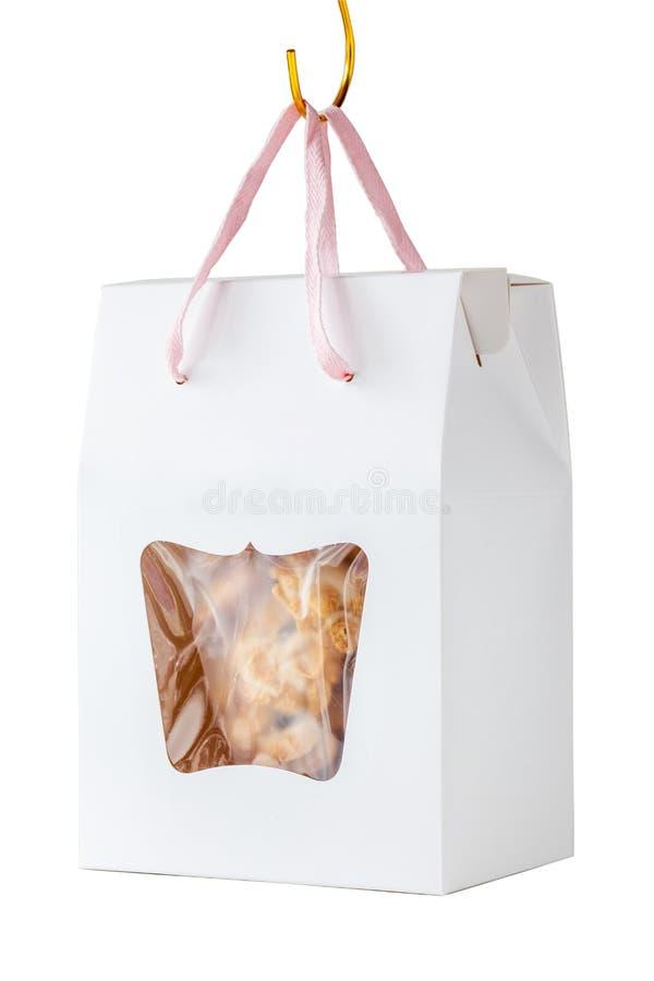 De eigengemaakte graangewassenkoekjes in document vakje gift hangt op witte bedelaars royalty-vrije stock afbeeldingen