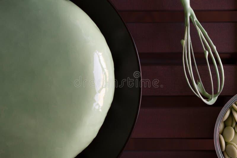 De eigengemaakte groene cake van de muntmousse met spiegelsuikerglazuur op een zwarte plaat, een het mengen zich metaal zwaait en stock afbeeldingen