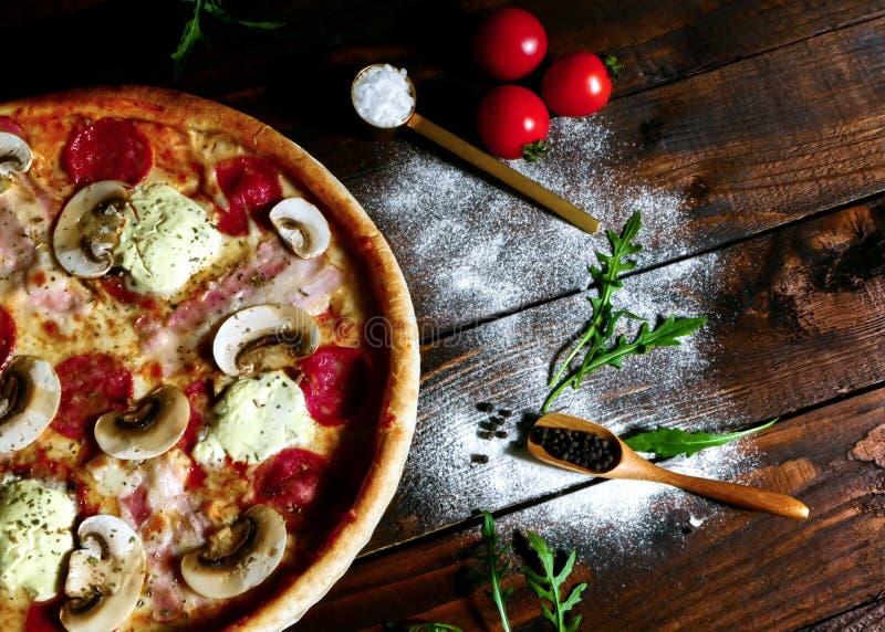 De eigengemaakte ham, salami en paddestoelpizza diende op een raad op een oude rustieke houten die keukenlijst door vers wordt om royalty-vrije stock afbeeldingen