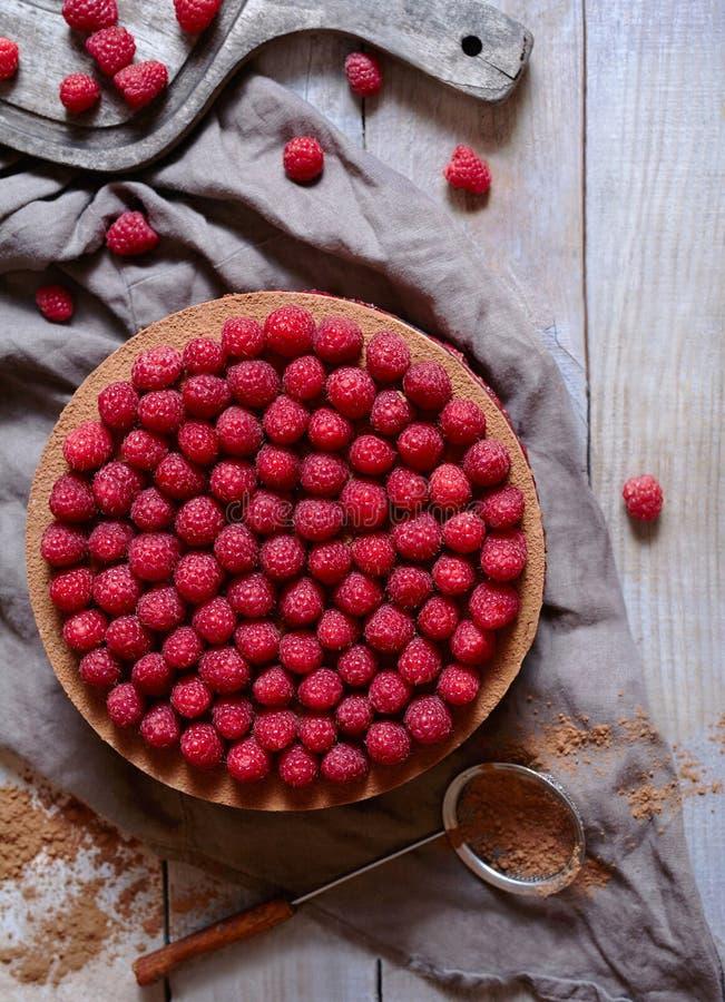 De eigengemaakte heerlijke kaastaart van de chocoladecake met frambozen op de rustieke houten lijst stock fotografie