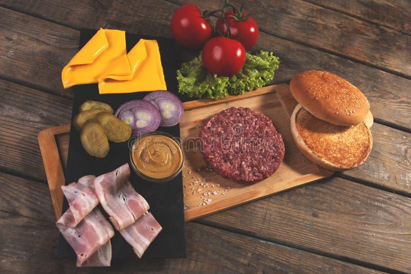 De eigengemaakte kaas van cheeseburger verse ingrediënten, broodje, zoutte komkommer, rundvleespasteitjes, bacon stock foto's
