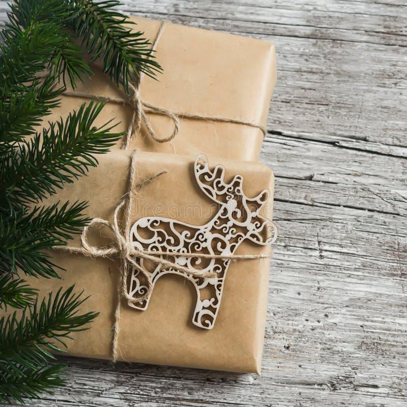 De eigengemaakte Kerstmisgift in kraftpapier-document, het houten ornament van Kerstmisherten, Kerstboom vertakt zich op rustieke stock afbeeldingen
