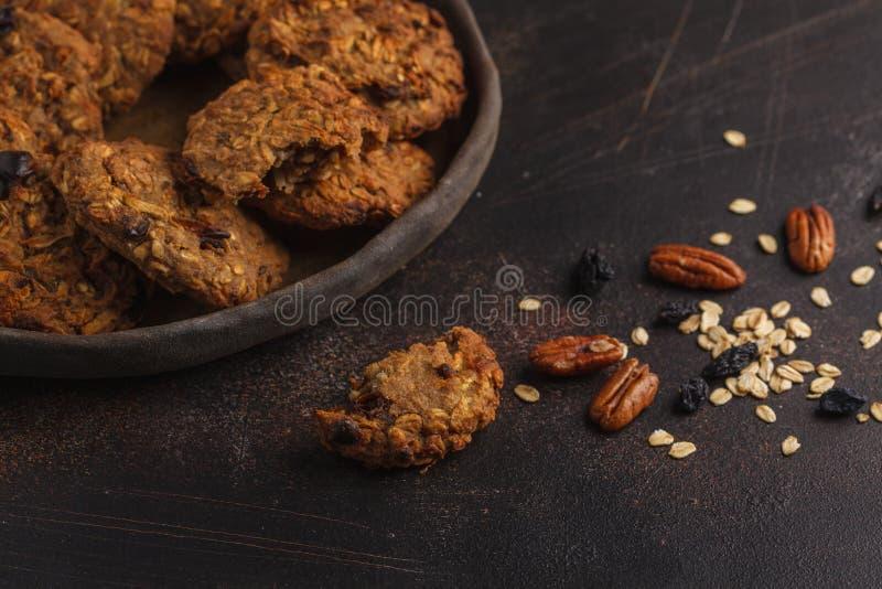De eigengemaakte koekjes van het veganisthavermeel met rozijnen, pecannoten en data H royalty-vrije stock afbeeldingen