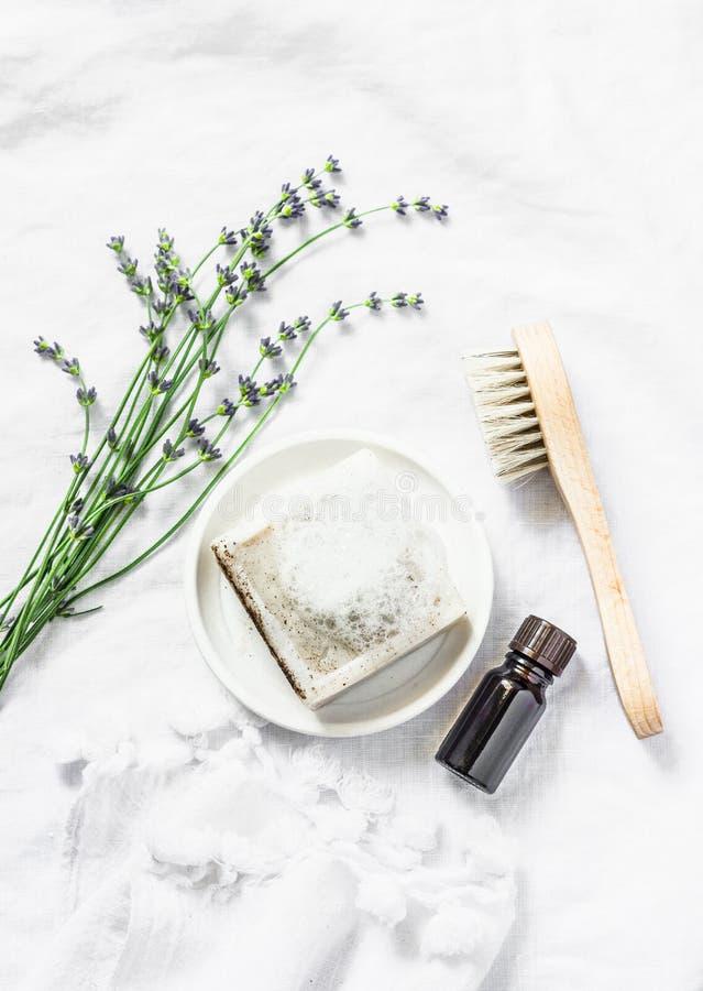 De eigengemaakte lavendelzeep, lavendel bloeit, gezichtsborstel, hoofdzaakolie op lichte achtergrond, hoogste mening stock foto's