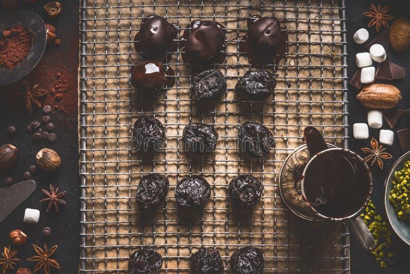 De eigengemaakte pralines en de truffels op donkere keuken dienen achtergrond met smeltende chocolade en ingrediënten in stock foto