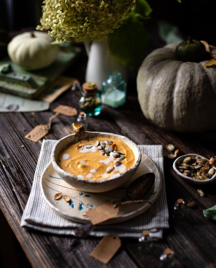 De eigengemaakte puree van de pompoensoep met pompoenzaden in ceramische kom op plaat met lepel royalty-vrije stock fotografie
