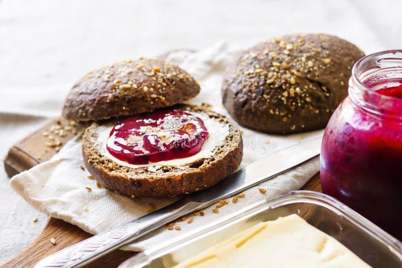De eigengemaakte roggebroodjes met lijnzaad, sesam en witte papaverzaden dienden met boter en jam stock foto