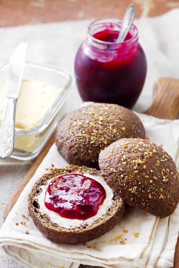 De eigengemaakte roggebroodjes met lijnzaad, sesam en witte papaverzaden dienden met boter en Jostaberry-jam stock foto