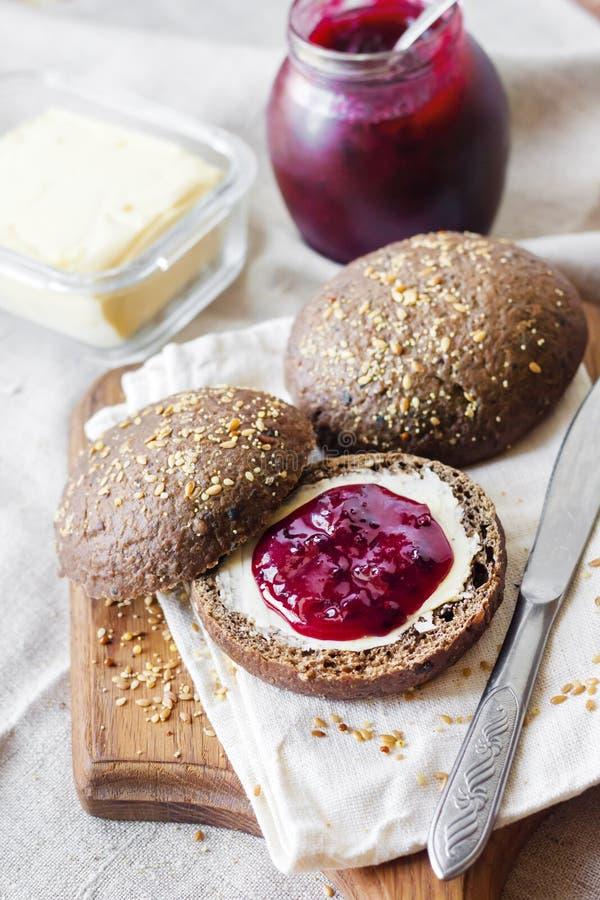 De eigengemaakte roggebroodjes met lijnzaad, sesam en witte papaverzaden dienden met boter en Jostaberry-jam royalty-vrije stock fotografie