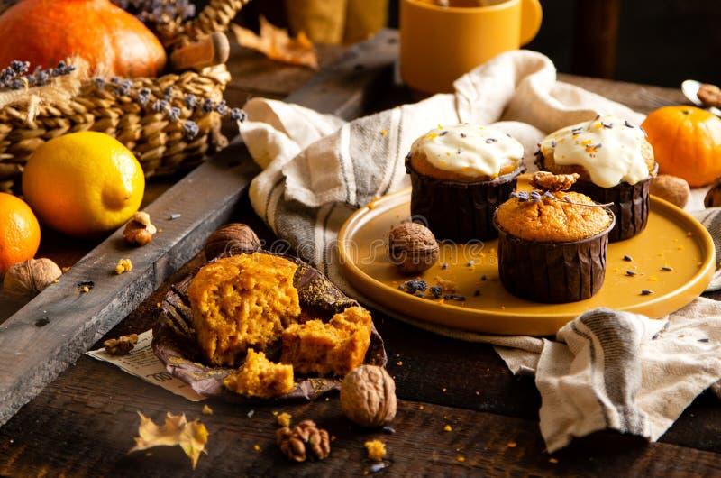 De eigengemaakte smakelijke muffins van de zoete sinaasappelpompoen of cupcakes met witte room, lavendel, schil, noten royalty-vrije stock afbeeldingen